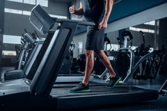Male person workout on running exercise machine Royalty Free Stock Image