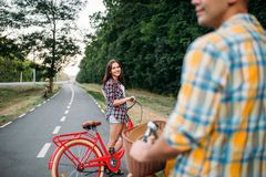 Male person and young woman riding on retro bikes Stock Image