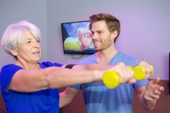 Male personal trainer coaching senior woman with weights. Male personal trainer coaching senior women with weights personal Stock Photography