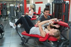 Male personal trainer helping young woman on work. Male personal trainer helping young women on her work Royalty Free Stock Image