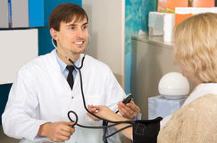Male pharmaceutist taking  mature patients blood pressure using. Sphygmomanometer in pharmacy drugstore Stock Photos