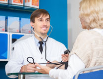 Male pharmaceutist taking patients blood pressure. Young male pharmaceutist taking mature patients blood pressure using  sphygmomanometer in pharmacy drugstore Royalty Free Stock Photos