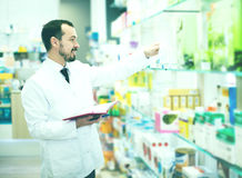 Male pharmacist checking assortment of drugs. Adult man pharmacist checking assortment of drugs in pharmacy Royalty Free Stock Images