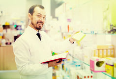 Male pharmacist checking assortment of drugs. Smiling man pharmacist checking assortment of drugs in pharmacy Royalty Free Stock Images