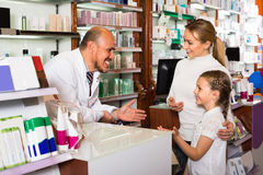 Male pharmacist at the counter in pharmacy. Cheerful smiling male pharmacist wearing white coat at the counter in pharmacy Royalty Free Stock Image