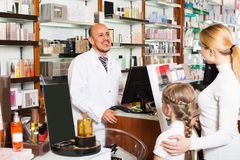 Male pharmacist at the counter in pharmacy. Happy male pharmacist wearing white coat standing at the counter in pharmacy Stock Images