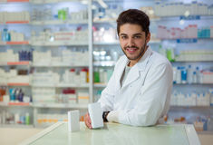 Male pharmacist dispensing medicine holding a box of ta Stock Photos