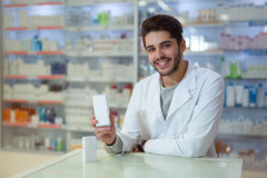 Male pharmacist dispensing medicine holding a box of ta Stock Photo
