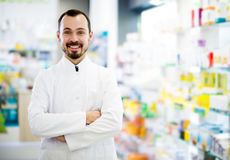 Male pharmacist displaying assortment of drugs. Man pharmacist displaying assortment of drugs in pharmacy Royalty Free Stock Image