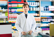 Male pharmacist  in drugstore. Smiling male pharmacist in white uniform posing in drugstore Stock Photography