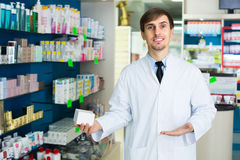 Male pharmacist  in drugstore. Smiling male pharmacist in white uniform at the workplace in drugstore Stock Photos
