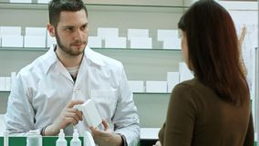 Male pharmacist and female client at pharmacy Stock Image