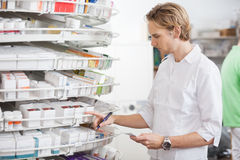 Male Pharmacist Filling Prescription. Young Caucasian male filling drug prescription in pharmacy Stock Photography