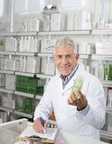 Male Pharmacist Holding Product While Writing On Clipboard Stock Photography