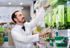 Male pharmacist looking for right medicine. Smiling happy cheerful positive male pharmacist looking for right medicine in pharmacy Stock Images