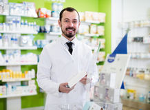 Male pharmacist offering right drug Stock Images