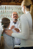 Male pharmacist in pharmacy. Customers with a kid and male pharmacist in white coat at the counter in pharmacy Stock Photography