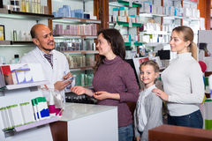 Male pharmacist in pharmacy. Smiling customers with a kid and male pharmacist in white coat at the counter in pharmacy Royalty Free Stock Photo