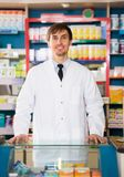 Male pharmacist posing in drugstore. Young smiling pharmacist posing near rack in drugstore Stock Photo