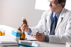 Male pharmacist sat at desk reading notes Stock Image
