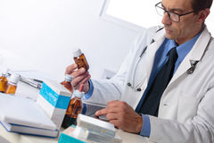 Male pharmacist sat at desk reading notes Stock Images