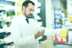 Male pharmacist searching for reliable drug. Adult man pharmacist searching for reliable drug in pharmacy stock photo