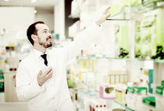 Male pharmacist searching for reliable drug Royalty Free Stock Image
