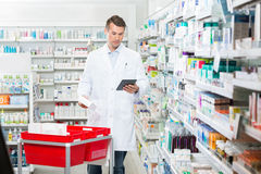 Male Pharmacist Updating Stock In Digital Tablet Stock Photos