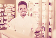 Male pharmacist wearing white coat standing  in drug store Royalty Free Stock Photo