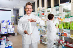 Male pharmacist wearing white coat standing  in drug store Royalty Free Stock Photos