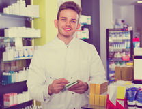 Male pharmacist wearing white coat standing  in drug store Stock Photo