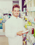 Male pharmacist wearing white coat standing  in drug store Royalty Free Stock Images