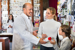 Male pharmacist working pharmaceutical store and consulting cust. Diligent male pharmacist in white coat working the pharmaceutical store and consulting Royalty Free Stock Photo