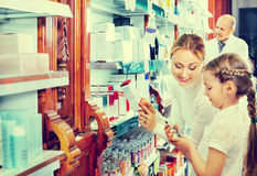 Male pharmacist working pharmaceutical store and consulting cust Stock Photo