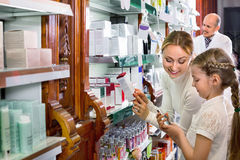 Male pharmacist working pharmaceutical store and consulting cust. Mature  friendly diligent male pharmacist in white coat working the pharmaceutical store and Royalty Free Stock Photo