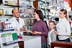 Male pharmacist working pharmaceutical store and consulting cust. Mature glad friendly male pharmacist in white coat working the pharmaceutical store and Stock Photography