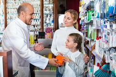 Male pharmacist working pharmaceutical store and consulting cust. Mature smiling diligent male pharmacist in white coat working the pharmaceutical store and Royalty Free Stock Images