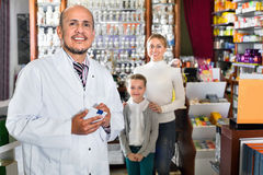 Male pharmacist working pharmaceutical store and consulting cust. Mature smiling friendly diligent male pharmacist in white coat working the pharmaceutical store Royalty Free Stock Images