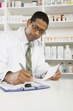 Male Pharmacist Working In Pharmacy Stock Photo