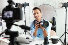 Male photo blogger recording video on camera. Indoors royalty free stock photography