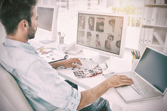 Male photo editor working on computer in a bright office. Side view of a male photo editor working on computer in a bright office Stock Images