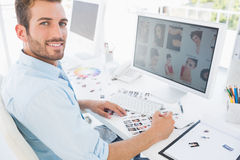 Male photo editor working on computer in a bright office Royalty Free Stock Photography