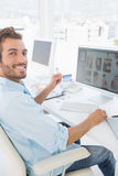 Male photo editor working on computer in office. Side view portrait of a male photo editor working on computer in a bright office Royalty Free Stock Photo