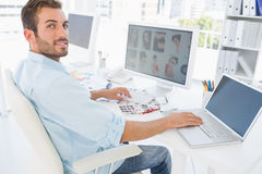 Male photo editor working on computer. Side view portrait of a male photo editor working on computer in a bright office Stock Photos
