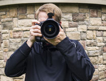 Male Photo Taker. Male photographer behind large camera lens with stone wall background Royalty Free Stock Photography