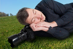 Male photographer with camera sleeping on meadow. Male photographer with digital camera sleeping on a meadow Royalty Free Stock Photos