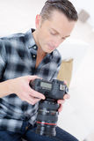 Male photographer checking photos in camera Stock Photography