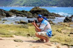 Male photographer with DSLR camera on the beach Royalty Free Stock Photo