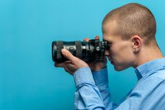 Male photographer examining his new camera. Side view of a young male photographer examining his new camera while standing against a blue background. Place for royalty free stock image