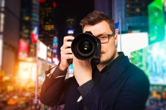 Male photographer in glasses with digital camera. Portrait of male photographer in glasses with digital camera, front view, night cityscape on background Stock Photo